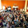 Den Scheck für eine ganz besondere Schulstunde überreicht Stefan Mittmann an Lehrerin Birgit Kox. Dahinter warten die Autoren auf ihren Einsatz.